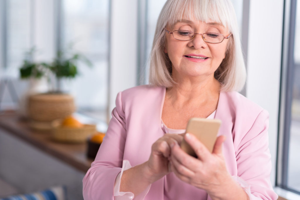 Senior woman with white hair and glasses looks at a smartphone while sending a message.