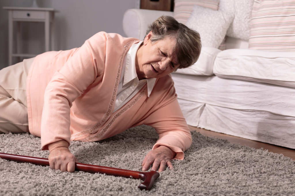 Older woman with cane needs emergency assistance after a fall.