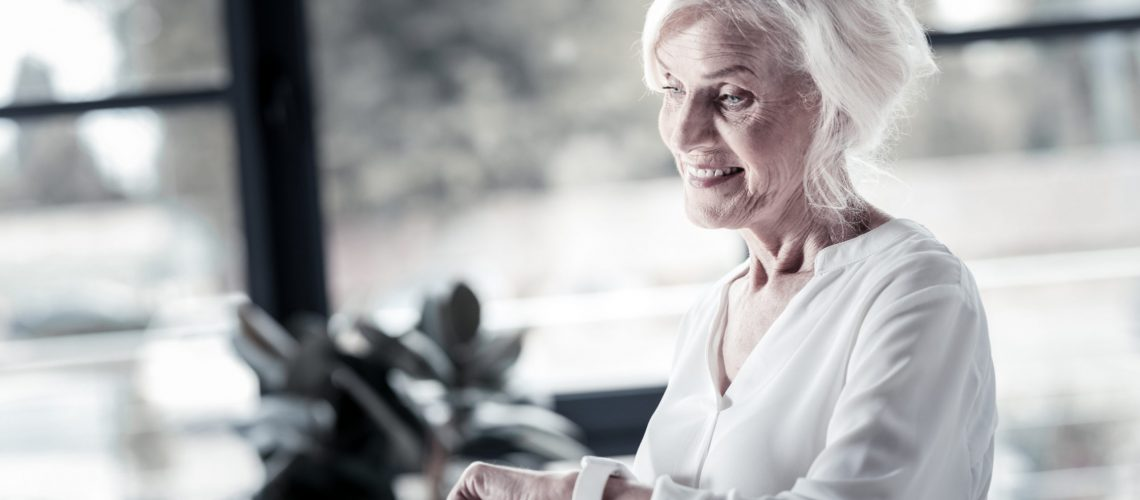 Senior woman smiles while looking at the smartwatch she is wearing.